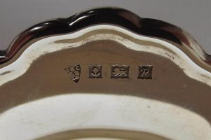 Closeup of hallmarks on silver petal dish
