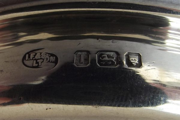 Closeup of hallmarks on silver pin tray